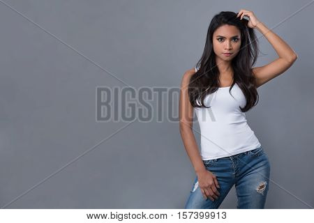 Beautiful Asian woman in plain white tank top and blue jeans posing with one hand slicking her hair back