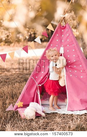 Smiling baby girl 2-3 year old holding toy teddy bear playing in wigwam outdoors. Looking at camera. Childhood.