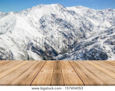 Wooden board empty table in front of blurred background. Perspective brown wood table over blur snow mountain landscape background - can be used mock up for display or montage your products.