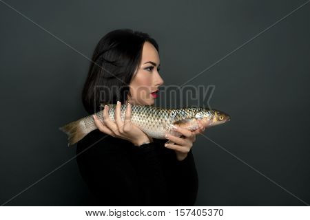 The woman in black dress holds live fish in hand The woman supports environmental protection.