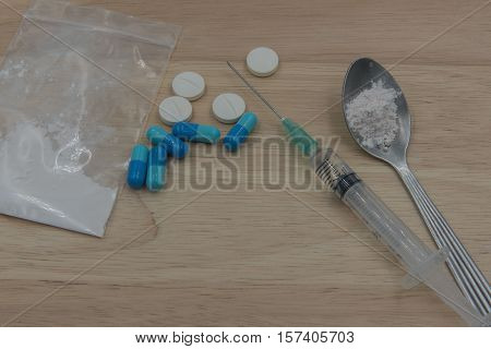 syringe and Drug and  spoon cooked heroin on a wooden background. in the studio.