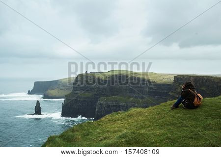 Girl sitting in the Cliffs of Moher in a foggy day