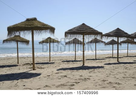 Row of straw umbrellas in the beach of Marbella Andalusia Spain.