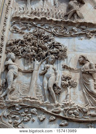 Orvieto - Duomo facade. The first pillar: scenes from Genesis. In the company of angels God forbids Adam and Eve eat the fruit from the tree