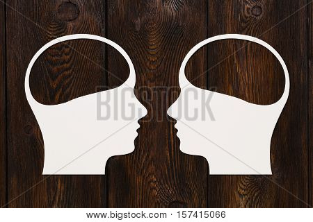 Paper heads with copyspace inside, dark wooden background, abstract conceptual image