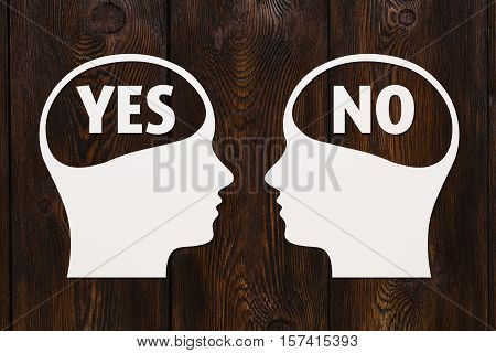Paper heads with yes and no text inside, dark wooden background, abstract conceptual image