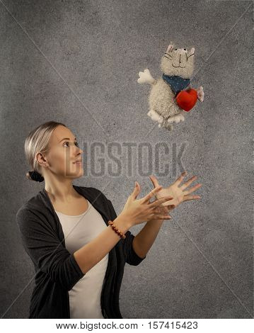 Pretty happy young blond woman in casual cloths catches plush cat toy with heart dreaming looking up against grey texture wall background with copy space