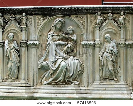 Madonna and Child with two angels. Panel of the Fonte Gaia (Fountain of Joy) Piazza del Campo Siena.
