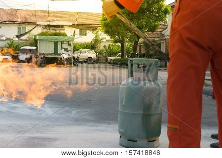 Many people preparedness for fire drill and training to use a fire safety tank in village at Bangkok Thailand. process in soft orange sun light style
