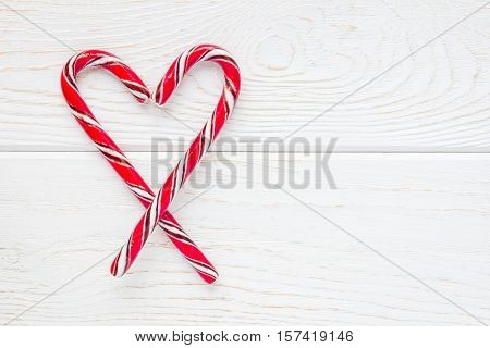 Crossed peppermint candy canes on white wooden background copy space top view