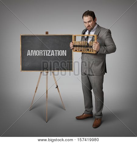 Amortization text on blackboard with businessman and abacus