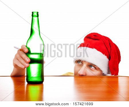 Young Man in Santa's Hat with the Beer at the Table on the White Background