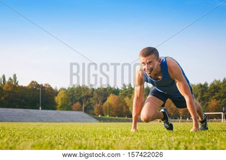 Man in low start position on old stadium. Athlete in starting position. Running jogging cardio sport active lifestyle concept.