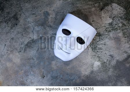 White anonymous mask on dark grunge texture