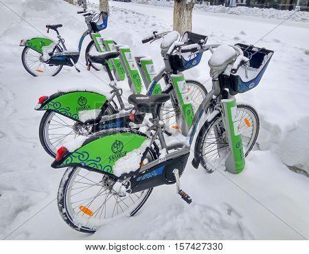 ALMATY KAZAKHSTAN - November 20 2016: The automated station rental bike under the snow in the city of Almaty Kazakhstan Almaty Kazakhstan - November 20 2016: The automated station rental bike under the snow in the city of Almaty Kazakhstan