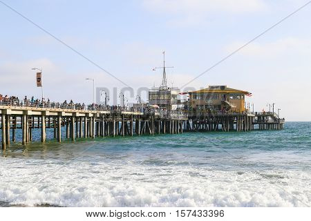 SANTA MONICA, USA - MAY 30, 2015: Crowd on the Santa Monica Pier with the restaurant and the harbor office in the back.