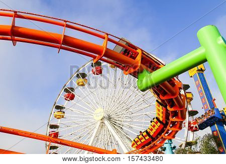 SANTA MONICA, USA - MAY 30, 2015: Ferris wheel West Coaster and Pacific Plunge drop tower in Pacific Park with people taking a ride.