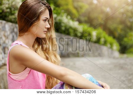 Sports, Determination And Endurance. Side View Of Attractive Woman With Long Hair In Sportswear Sitt