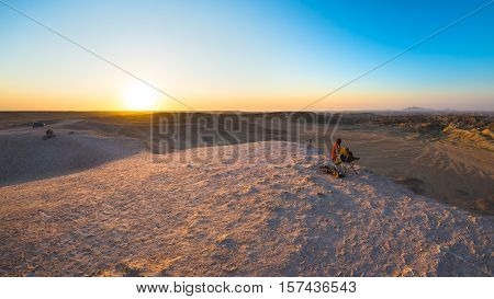 Rear View Of Woman Sitting On Rocks And Looking At Expansive View Over The Scenic Namib Desert At Du