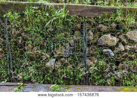 Chain link protecting rocks from falling from the side of a hill