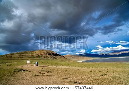 Solo female cyclist on the bicycle in the stunning remote part of Central Tibet