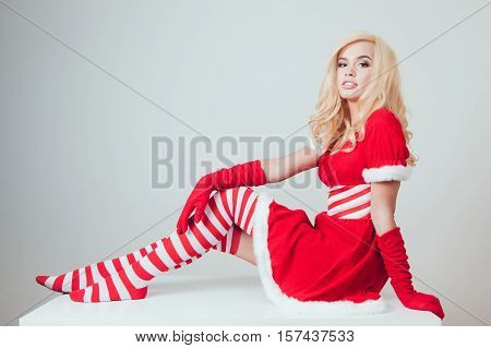 Beautiful blonde snow maiden sitting on a white background