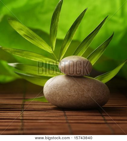 zen stones and palm leaf on bamboo mat
