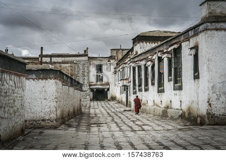 Monk walking in the courtyard between buildings in the compound of the Tibetan Monastery in Shigatse in central Tibet