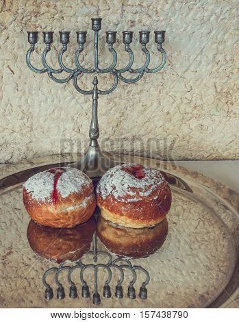 Festive sweet donuts and menorah are traditional symbols of Hanukkah holida. Selective focus. Image toned for inspiration of retro style.