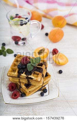 Belgian Waffles With Raspberries, Blueberries And Mint, Covered With Liquid Chocolate.delicious Waff