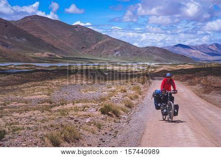 Single female cyclist on the bicycle on the remote road in Central Tibet