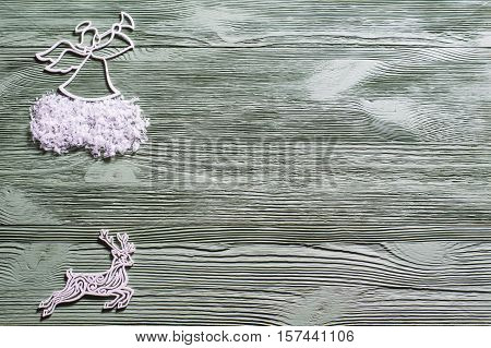 Christmas angel with wings and trumpet on cloud heralds the arrival of Christmas. Angel and reindeer on a wooden background flat lay. Layout greeting card for winter holidays Christmas New Year.