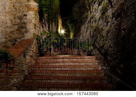 Narrow passage and stairs at night in San Gimignano in Tuscany Italy. Blurred plants in pots moved by wind