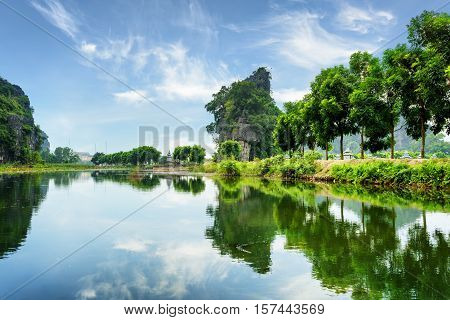 Amazing Natural Karst Towers And Green Trees Reflected In Water