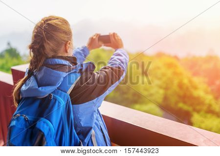 Young Female Tourist In Rays Of Sunlight With Smartphone