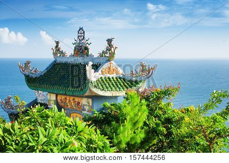 Tile Roof Of Buddhist Temple Among Foliage On Sea Background
