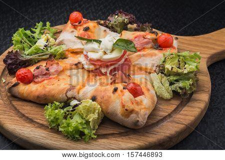 Italian Pizza Calzone With Tomato, Salad And Mozzarella