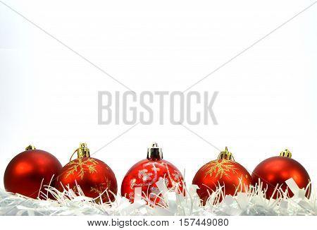 Five red Christmas balls a white wreath put horizontally down