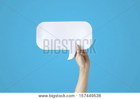 Human Hands Holding White Speech Bubble Over Blue Background - Balloon Speech Bubble Concept