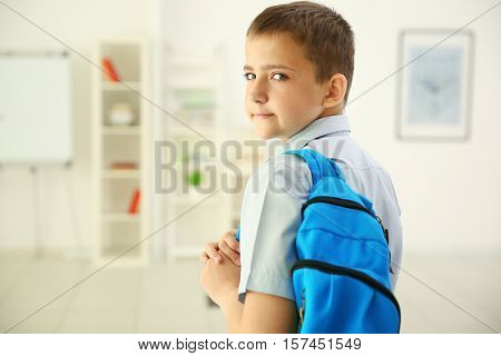 Cute schoolboy on light background