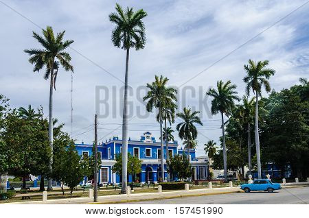 CIENFUEGOS, CUBA - MARCH 22, 2016: Blue colonial building and palm trees in Cienfuegos Cuba