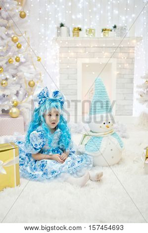 Little girl with blue hair and blue bow and wearing a blue dress sitting in a New Year's interior with a snowman