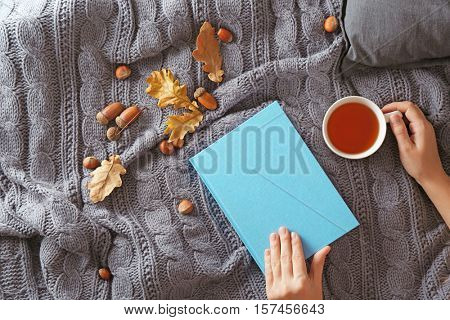 Female hands with book and cup of tea on bed