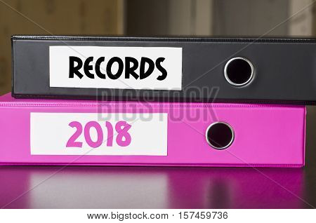 Bright office folders over dark background and records 2018 text concept