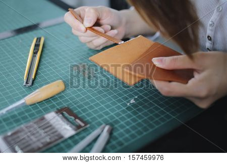 Women working with leather using crafting tools.