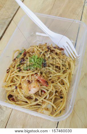 Spaghetti Aglio Olio inside take away box with fork.