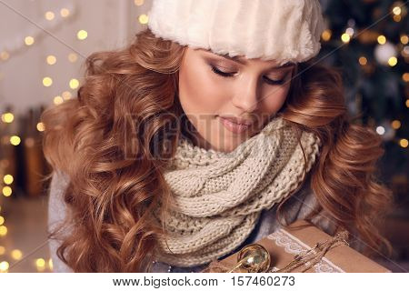 fashion studio photo of beautiful charming woman with curly hair in warm cozy winter clothes posing near Christmas tree poster