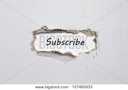 The word subscribe appearing behind torn paper