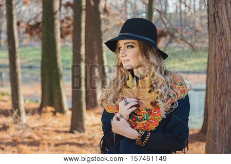 Autumn portrait of a hippie young woman wearing a hat