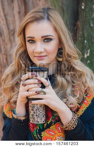 Winter portrait of a beautiful young woman, drinking hot tea